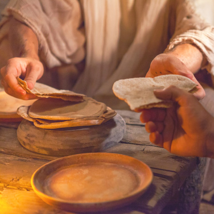 Image of Jesus breaking and sharing bread, depicting Goal #1: Abundant Spiritual Opportunities