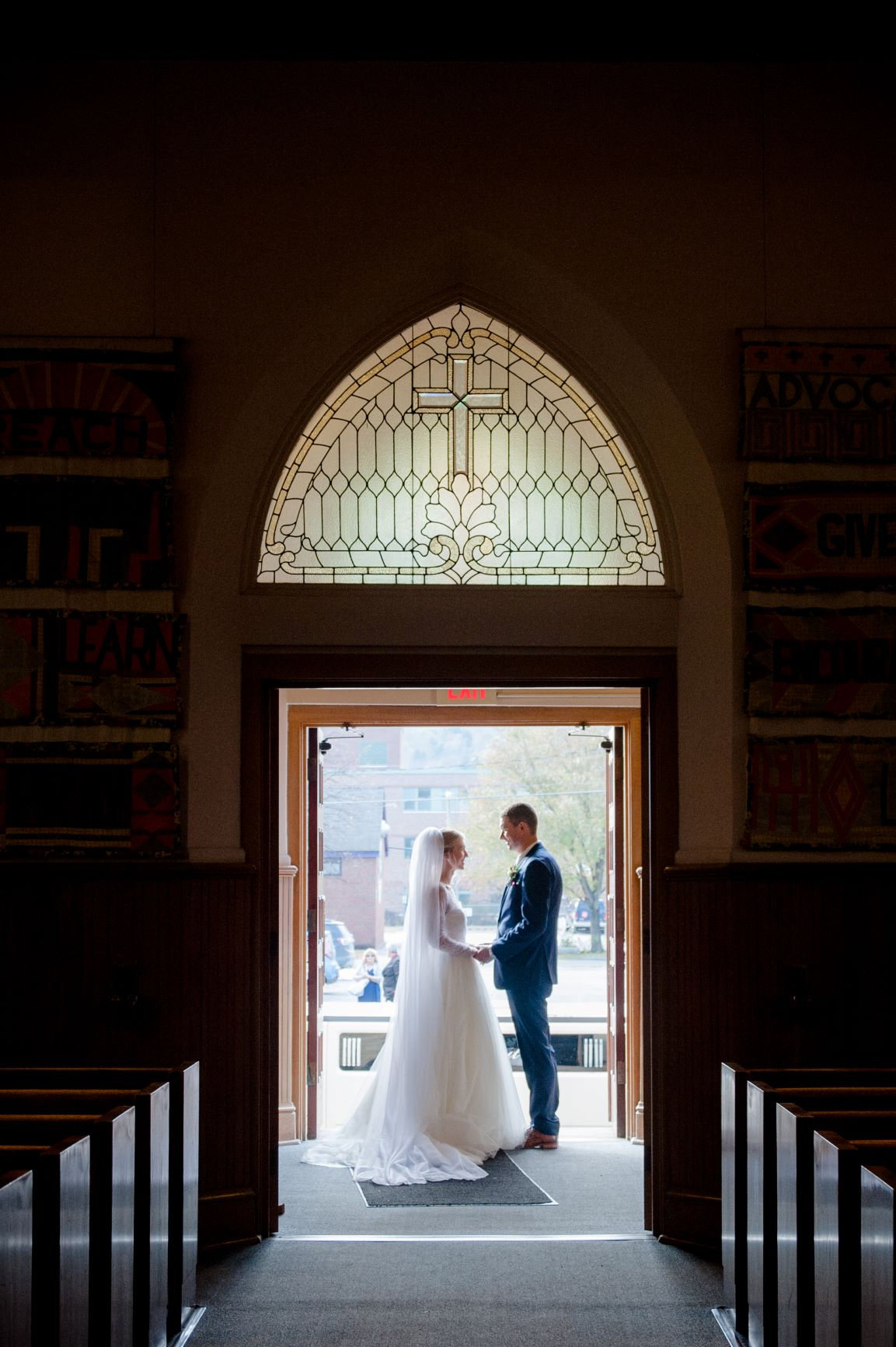 A photo of the wedding of Allie (Robinson) and Allan Runions. Standing facing each other at the church entryway.
